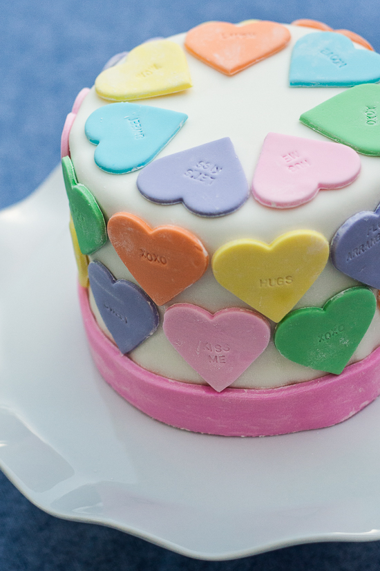 Pastel fondant hearts and a customizable letter stamp help create a personalized conversation hearts cake. It's the perfect cake for Valentine's Day!