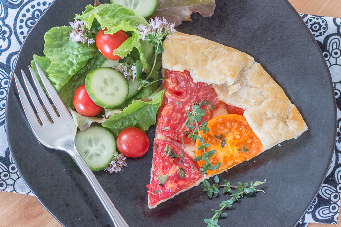 Simple yet stunning, this tomato galette turns juicy, ripe tomatoes into a satisfying, delicious meal. Gouda and smoked mozzarella provide a rich, slightly smoky backdrop to the bright tomato flavor.