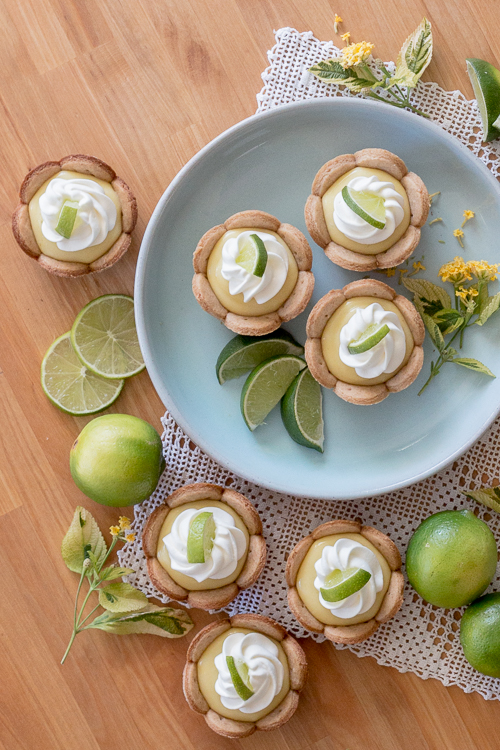 Homemade graham cracker cups filled with sweet, tangy lime curd come together in adorable little lime tarts. Simple to serve, these eat-by-hand treats make a perfect party dessert.