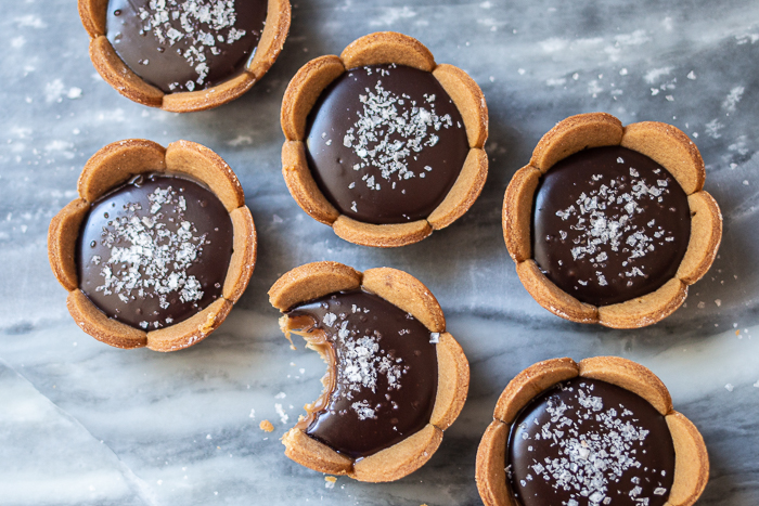 Spicy gingerbread cookie crusts provide a bold, flavorful backdrop for sweet caramel and rich, smooth ganache in these Mini Salted Caramel-Chocolate Tarts.