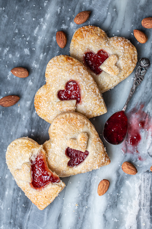 Jammy Almond Hand Pies feature nutty almond filling and fruity jam tucked inside flaky pastry dough. Shaped like hearts, they're perfect for Valentine's Day!